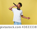 Young handsome African American Male Singer Performing with Microphone. Isolated over yellow gold 43633338