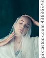 Beautiful bride looking over her veil 43636543