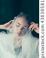 Beautiful bride looking over her veil 43636581
