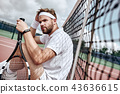 Relaxing after good game. Cheerful man at the tennis net resting sitting on tennis court 43636615