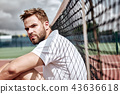 Relaxing after good game. Cheerful man at the tennis net resting sitting on tennis court 43636618