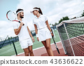 They play like a team. Beautiful young woman and man holding tennis racket and discussing set 43636622