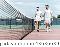 Enjoying spending time on the court. Beautiful young couple walking on the tennis court with smile. 43636639