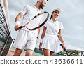 Enjoying spending time on the court. Beautiful young couple walking on the tennis court with smile. 43636641