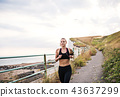 Young sporty woman runner with earphones running by sea in nature. 43637299