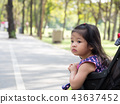 Little asian girl sitting in a Stroller at park. 43637452