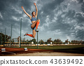Female athlete performing a long jump during a competition 43639492