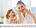 Mother and daughter caring for skin 43639939