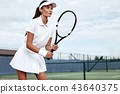 Woman playing tennis and waiting for the service 43640375