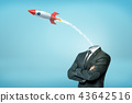 A businessman with crossed arms and with a small launched old-school rocket instead of his head. 43642516