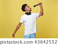 Young handsome African American Male Singer Performing with Microphone. Isolated over yellow gold 43642552