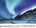 Northen light above mountains and ocean. 43644602