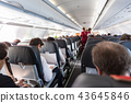 Interior of commercial airplane with passengers on their seats during flight. 43645846