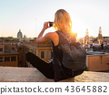 Female tourist taking mobile phone photo of Piazza di Spagna, landmark square with Spanish steps in 43645882
