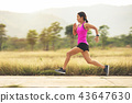 young woman runner running at public park 43647630