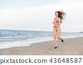 Attractive woman runs on sand beach in summer. 43648587