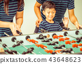 Happy kid playing foosball table with family. 43648623