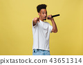 Attractive young dark-skinned man with afro haircut in white t shirt, gesticulating with hands and 43651314