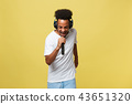 Attractive young dark-skinned man with afro haircut in white t shirt, gesticulating with hands and 43651320