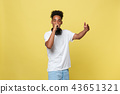 Attractive young dark-skinned man with afro haircut in white t shirt, gesticulating with hands and 43651321
