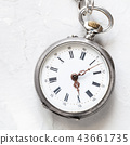 used silver pocket watch on light gray plaster 43661735