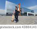 Fashionable European business man in perfect suite walk on the street, using skateboard longboard 43664143