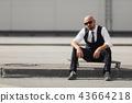 stylish businessman sitting on longboard near modern building 43664218
