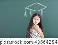 girl in graduation cap with thinking gesture 43664254
