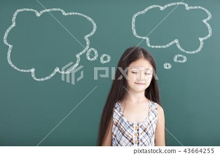 beautiful little girl thinking before chalkboard 43664255