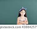 smiling little girl stand before empty chalkboard 43664257