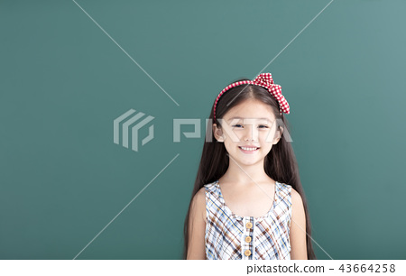 smiling little girl stand before empty chalkboard 43664258