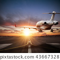 Private jet plane landing on runway in sunset 43667328