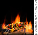 Delicious skewers on grill with Fire flames. 43667859