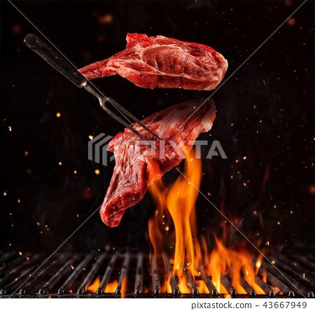Flying pieces of pork chops steaks on black 43667949