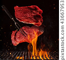 Flying pieces of beef steaks on black 43667953
