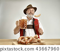 Germany, Bavaria, Upper Bavaria, man with beer dressed in traditional Austrian or Bavarian costume 43667960