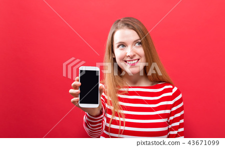 Young woman holding out a cellphone 43671099