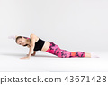 Young sportwoman stretching muscles on white 43671428