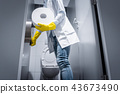 Janitor woman changing paper in public toilet 43673490