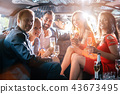 Group of party people in a limo drinking 43673495