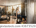 Attractive woman sitting at the abductor machine while exercising for buttocks 43673520