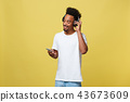 Portrait good-looking african male model with beard listening to music. Isolated over yellow 43673609