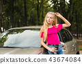 Girl pose near car with glasses and cup 43674084