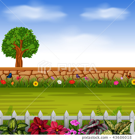 the stone wall with the tall tree and flowers 43686018