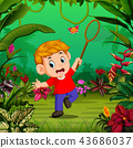 the boy tries to catch a butterfly in the forest 43686037
