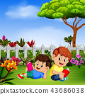 two children reading book in the yard 43686038