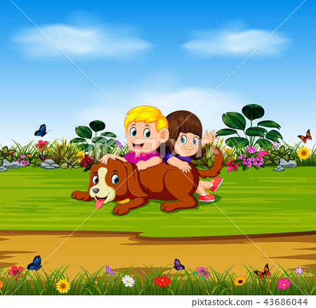 the boy and the girl are playing with their dog 43686044