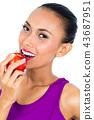Smiling woman eating apple 43687951