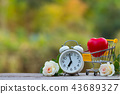 Red heart shape in shopping cart and white clock 43689327