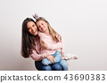 A small girl with crown headband and her mother sitting in a studio. 43690383